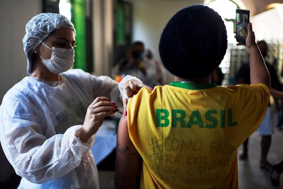 File: A health worker administers a Covid vaccine dose to a resident as he takes a selfie, during mass vaccination at the Ilha Grande island, one of the most famous tourist spots in Rio de Janeiro state, Brazil (Reuters)
