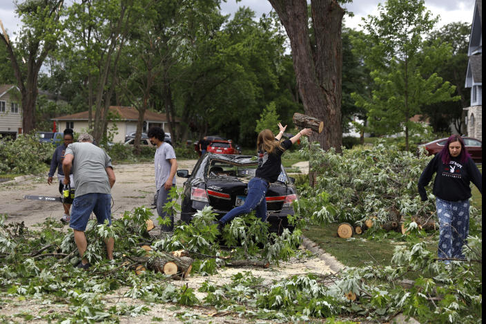 Woodridge, Ill., residents clear trees off a damaged car after a tornado passed through the area on Monday, June 21, 2021. (AP Photo/Shafkat Anowar)