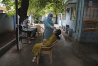 A woman gets her nasal swab sample taken to test for the coronavirus at a government health center in Hyderabad, India, Wednesday, July 15, 2020. As India's coronavirus caseload approaches 1 million, lockdowns are being reimposed in parts of the country as governments try to shield the health system from being overwhelmed. (AP Photo/Mahesh Kumar A.)