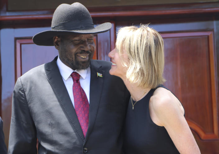 South Sudan's President Salva Kiir, left, and U.S. Ambassador to the U.N. Kelly Craft react as they talk, Sunday, Oct.20, 2019, while posing for pictures with the rest of the U.N. Security Council during the group's one-day visit to the capital Juba on Sunday to discuss the country's peace deal. Machar made an impassioned plea to a visiting United Nations Security Council delegation that met with him and President Salva Kiir to urge speedier progress in pulling the country out of a five-year civil war.(AP Photo/Sam Mednick)