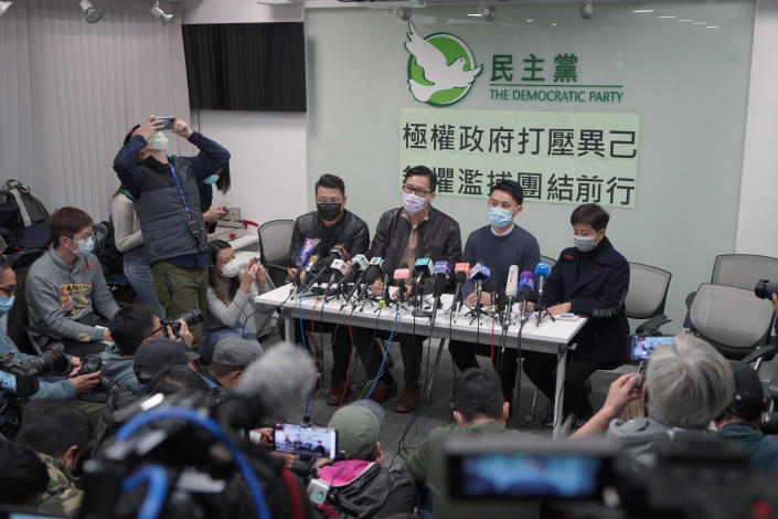 """Former Democratic Party legislators Andrew Wan, left, Lam Cheuk-ting, second left, and Helena Wong, right, attend a press conference after being released on bail in Hong Kong, Friday, Jan. 8, 2021. Some former Hong Kong legislators and pro-democracy activists were released on bail late Thursday, after being arrested under Hong Kong's national security law as part of Wednesday's mass arrests of 53 people. The Chinese in the background reads """"Totalitarian government suppresses dissidents, fearless of indiscriminate arrest, we walk forward together."""" (AP Photo/Kin Cheung)"""