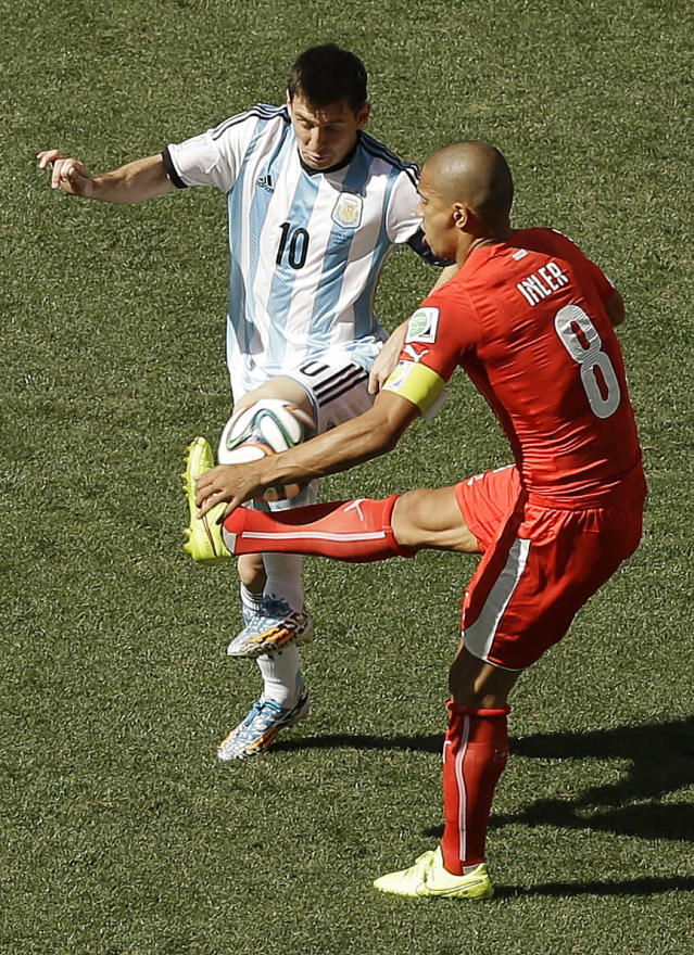 Argentina's Lionel Messi, left, challenges for the ball with Switzerland's Goekhan Inler during the World Cup round of 16 soccer match between Argentina and Switzerland at the Itaquerao Stadium in Sao Paulo, Brazil, Tuesday, July 1, 2014. (AP Photo/Thanassis Stavrakis)