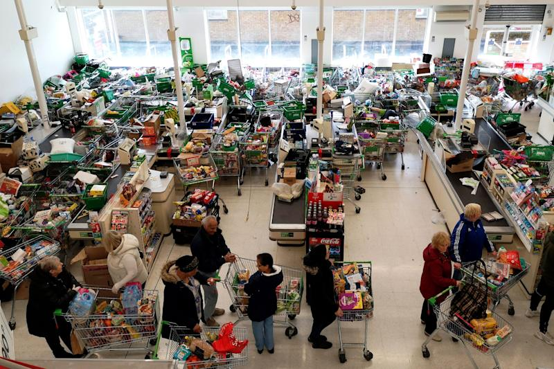 Trolleys piled high for delivery are seen as shoppers queue at the checkout of a supermarket in London on March 14, 2020, as consumers worry about product shortages, leading to the stockpiling of household products due to the outbreak of the novel coronavirus COVID-19. Photo: JUSTIN TALLIS/AFP via Getty Images