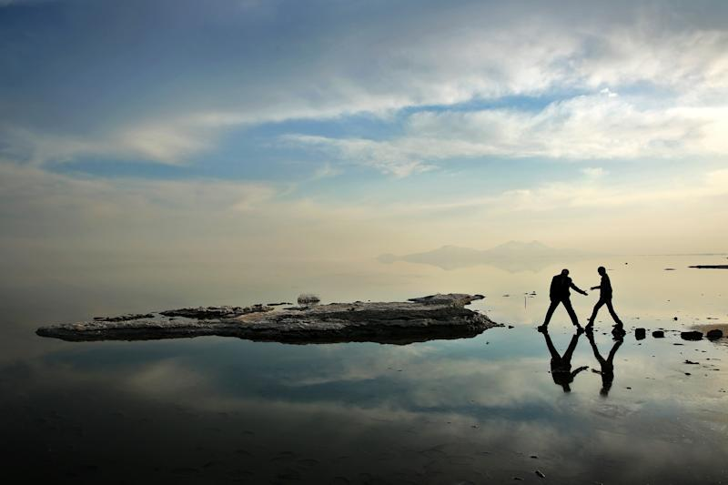 In this Saturday, Feb. 15, 2014 photo, two men walk toward salt-covered rocks that were once deep underwater at Lake Oroumieh, in northwestern Iran. Oroumieh, one of the biggest saltwater lakes on Earth, has shrunk more than 80 percent to 1,000 square kilometers (nearly 400 square miles) in the past decade, mainly because of climate change, expanded irrigation for surrounding farms and the damming of rivers that feed the body of water, experts say. (AP Photo/Ebrahim Noroozi)