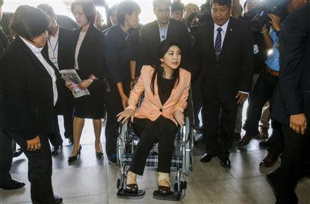 Thailand's Prime Minister Yingluck Shinawatra arrives on a wheelchair at the Royal Police Cadet Academy in Nakorn Pathom province