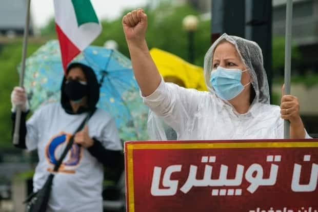 A woman dons a raincoat and chants during the North York, Ont., demonstration on Friday, June 18, 2021, in spite of the rain. (Sam Nar/CBC - image credit)