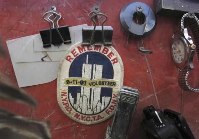 In this Tuesday, Jan. 8, 2019 photo, a badge remembering the Sept. 11, 2001, terrorists attacks hangs in the work area of a stone cutter at Rock of Ages in Barre, Vt. Stone cutter and fellow firefighter Andy Hebert is working on a permanent dedication to ground zero rescue and recovery workers expected to be unveiled in late May at the National September 11 Memorial & Museum in New York. (AP Photo/Lisa Rathke)