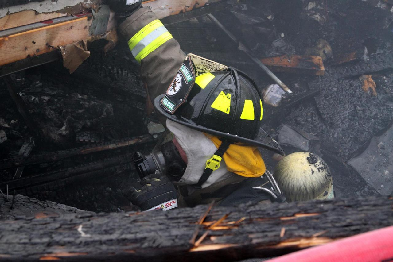 A Wrights Corners interior firefighter searches the burned out basement for a missing girl after an explosion on Tuesday, July 24, 2012 in Wilson, N.Y. The blast leveled the house killing a girl and injuring her parents and two siblings, authorities said. Sarah Johnson's body was found in the debris at the rear of the home, Niagara County Undersheriff Michael Filicetti said. Authorities weren't sure of her age but believe she was between 12 and 14. Filicetti said her parents and two siblings were blown clear and were found in the front yard by the first deputy to arrive on the scene. All four were being treated at a Buffalo hospital for serious injuries, he said. (AP Photo/Stephen M Wallace)