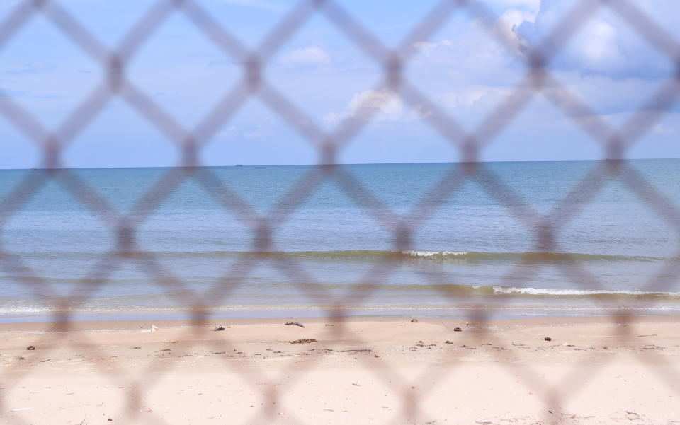 The beach is seen through steel wire net fence in Vung Tau, Vietnam, Monday, Sept. 20, 2021. In Vung Tau, just outside Ho Chi Minh city, streets are sealed and checkpoints are set up to control the movement of people. Barbed wire, door panels, steel sheets, chairs and tables are among materials being used to fence up alleys and isolate neighborhoods.(AP Photo/Hau Dinh)