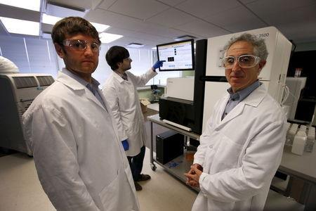 Technician Mike Lattari (rear) works on a genetic sequencing machine as Alan Shuldiner (R) and Aris Baras, co-heads of the Regeneron Genetics Center, pose for a photo at a Regeneron Pharmaceuticals Inc. laboratory at the biotechnology company's headquarters in Tarrytown, New York March 24, 2015. REUTERS/Mike Segar