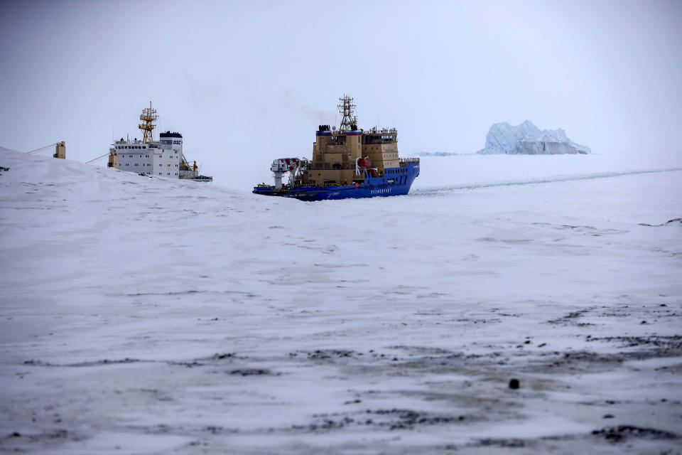 An Icebreaker makes the path for a cargo ship with an iceberg in the background near a port on the Alexandra Land island near Nagurskoye, Russia, Monday, May 17, 2021. Once a desolate home mostly to polar bears, Russia's northernmost military outpost is bristling with missiles and radar and its extended runway can handle all types of aircraft, including nuclear-capable strategic bombers, projecting Moscow's power and influence across the Arctic amid intensifying international competition for the region's vast resources. (AP Photo/Alexander Zemlianichenko)