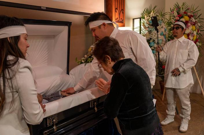Bao Nguyen, right, records the funeral of his father Dung Tan Nguyen as his brother Michael Chambon, second from right, gives one last touch while standing alongside Trang Nguyen, left, and Kim Anh Dinh, on Wednesday, May 6, 2020, during the coronavirus outbreak. Only four family members were permitted inside the funeral chapel and the family members were torn between grieving and taking turns holding the camera to live stream the service. Other mourners sat outside or in their cars trying to view the live stream but got frustrated because the video quality was bad.