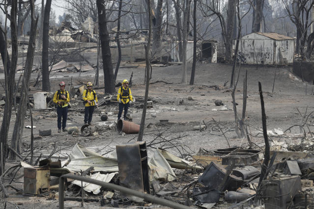 <p>San Bernardino County Fire department firefighters assess the damage to a neighborhood in the aftermath of a wildfire, July 29, 2018, in Keswick, Calif. (Photo: Marcio Jose Sanchez/AP) </p>