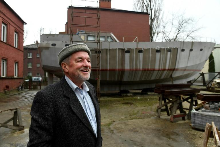 Ship Captain Waldemar Rzeznicki stands in front of a steel schooner named 'Father Boguslaw' under construction, at the courtyard of a homeless shelter run by Catholic Fathers, in Warsaw