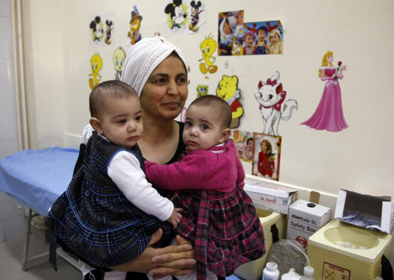 Woman carrying twin girls waits before they receive polio vaccinations at a medical centre in Damascus