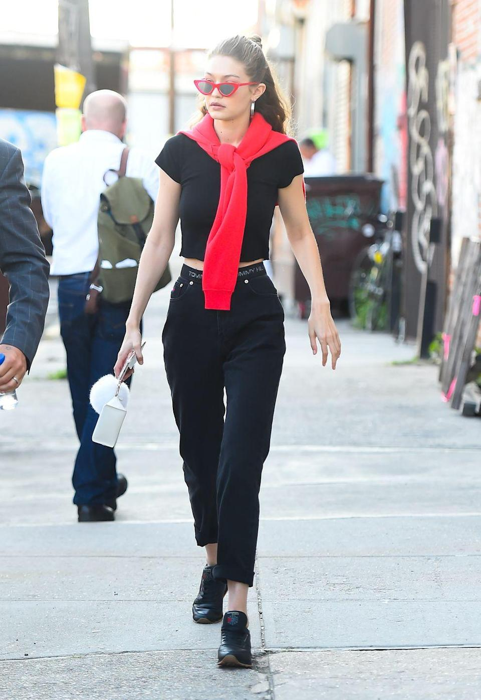 <p>In a black top and pants with a red sweater tied around her shoulders and red Adam Selman x Le Specs Last Lolita sunglasses while out in New York City. </p>