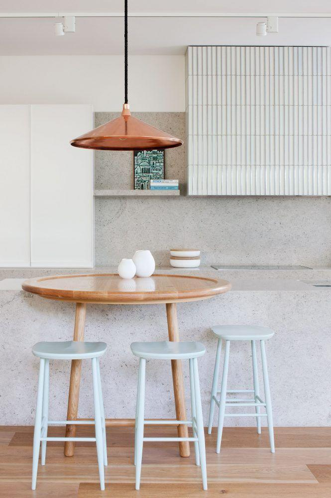 <p>The light wood tones and metallic pendant warm up the otherwise cool space in this kitchen designed by Hecker Guthrie. This space also proves that a bistro round bistro table situated over the island makes a classic kitchen layout so much more interesting. And it's even fresher when you paint your bar stools a buoyant shade of mint green hue and hang a copper pendant light overhead.</p>