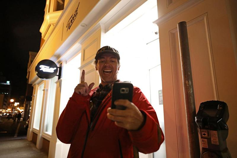 Ian Power takes a selfie outside the Tweed store as he lines up to purchase legal recreational marijuana in St John's, Newfoundland (Chris Wattie/Reuters)