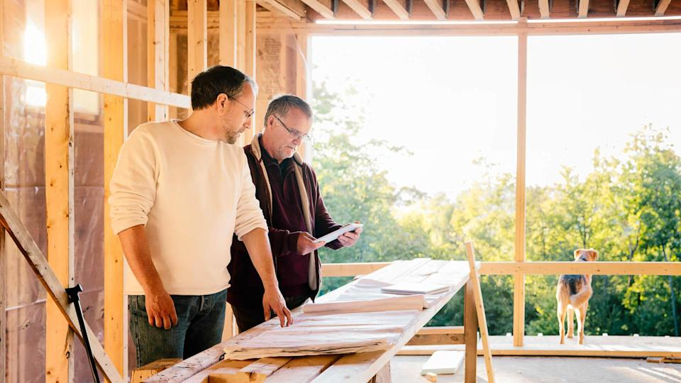Architect comparing physical plans to tablet version with a the contractor.