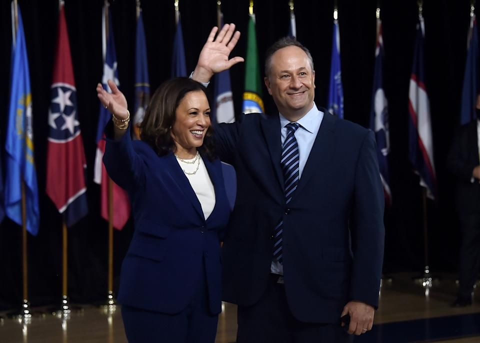 Democratic vice presidential running mate Kamala Harris and her husband Douglas Emhoff wave from the stage after the first Biden-Harris press conference in Wilmington, Delaware, on August 12, 2020.
