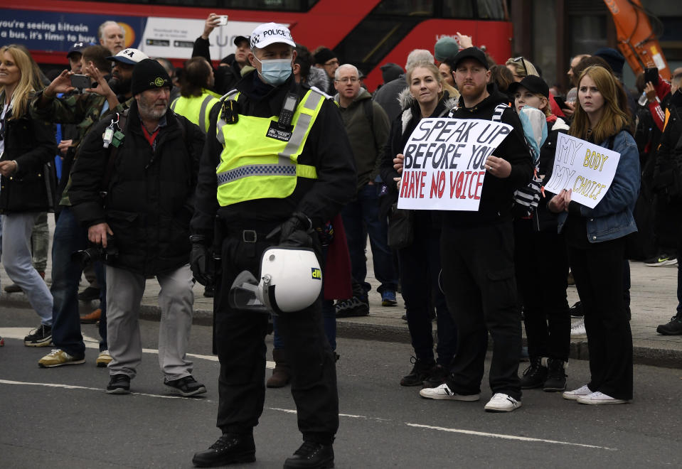 Police stand by as people without face masks attend a protest against government restrictions to curb the spread of the coronavirus, in London, Saturday, March 20, 2021. (AP Photo/Alberto Pezzali)