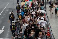 People wearing face masks march during a Black Lives Matter protest following the death in Minneapolis police custody of George Floyd, in Tokyo