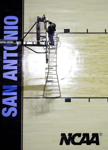 A worker prepares for the NCAA college basketball tournament games, Wednesday, March 19, 2014, in San Antonio. Play in San Antonio begins Friday morning when Nebraska faces Baylor. (AP Photo/Eric Gay)