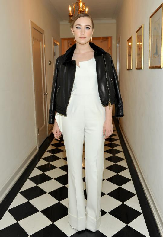 Saoirse Ronan attends the BAFTA Awards in Los Angeles, CA wearing a sleek white jumpsuit and leather jacket draped just so over the shoulders. (Photo: Getty)