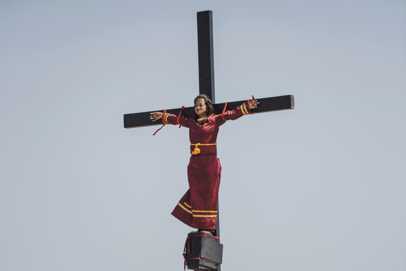 Mary Jane Sazon, the only woman to join in the crucifixion in the village this year, remains calm while she is nailed on a wooden cross as part of Good Friday rituals in the village of San Pedro Cutud, Pampanga province, northern Philippines, Friday, April 19, 2019. Sazon has joined the crucifixion ritual for more than a dozen times, according to tourism officials. She says this year's devotion is dedicated to her sickly mother. Over a thousand Filipino Roman Catholic devotees and tourists flocked to a farming village north of Manila on Friday to witness the crucifixion of several devotees in a costumed reenactment of Jesus Christ's sufferings, a gory annual tradition church leaders frown upon. (AP Photo/Iya Forbes)