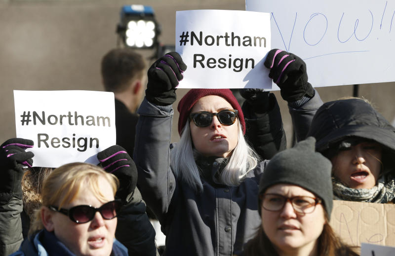 FILE - In this Saturday, Feb. 2, 2019 file photo, demonstrators hold signs and chant outside the Governors Mansion at the Capitol in Richmond, Va., calling for the resignation of Gov. Ralph Northam. A decades-old photo of two people in Ku Klux Klan and blackface costumes was discovered in his medical school yearbook page. Two months after Northam's political career was all but dead, his life seems mostly back to normal. (AP Photo/Steve Helber)