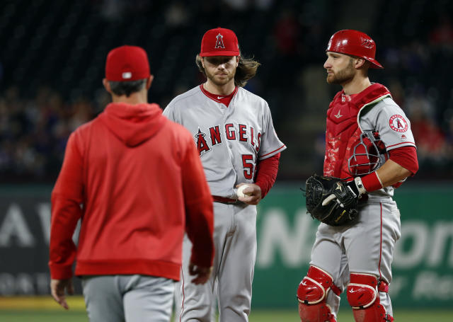 Los Angeles Angels manager Brad Ausmus, left, walks out to take the ball from relief pitcher Dillon Peters, center, as catcher Jonathan Lucroy stands by during the seventh inning of the team's baseball game against the Texas Rangers in Arlington, Texas, Tuesday, April 16, 2019. (AP Photo/Tony Gutierrez)