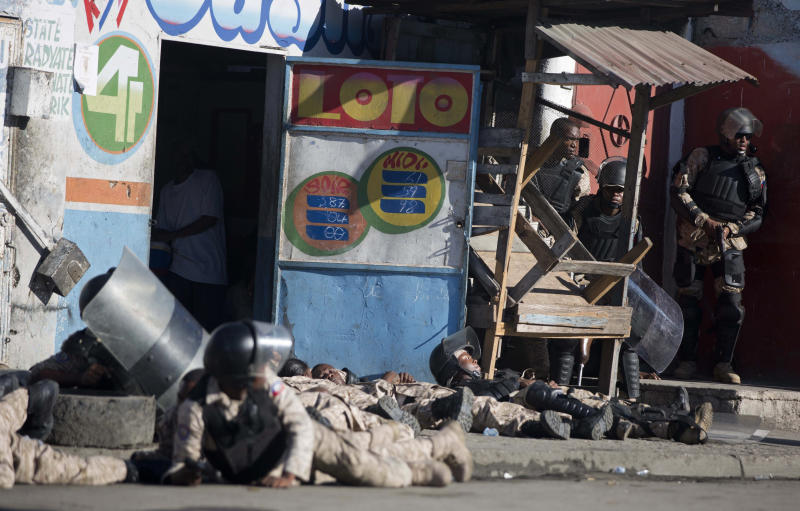 National police take cover as gun shots ring out at the end of a ceremony marking the 212th anniversary of the assassination of independence hero Gen. Jean-Jacques Dessalines in Port-au-Prince, Haiti, Wednesday, Oct. 17, 2018. At least three people were injured when shots were fired at the ceremony. (AP Photo/Dieu Nalio Chery)