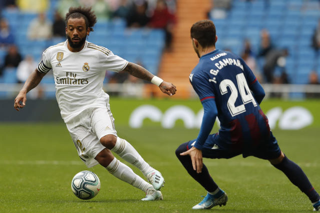 Real Madrid's Marcelo, left, duels for the ball with Levante's Jose Campana during the Spanish La Liga soccer match between Real Madrid and Levante at the Santiago Bernabeu stadium in Madrid, Spain, Saturday, Sept. 14, 2019. (AP Photo/Bernat Armangue)