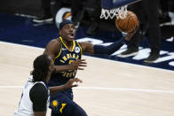 Indiana Pacers' Aaron Holiday (3) puts up a shot against Minnesota Timberwolves' Naz Reid (11) during the second half of an NBA basketball game, Wednesday, April 7, 2021, in Indianapolis. (AP Photo/Darron Cummings)