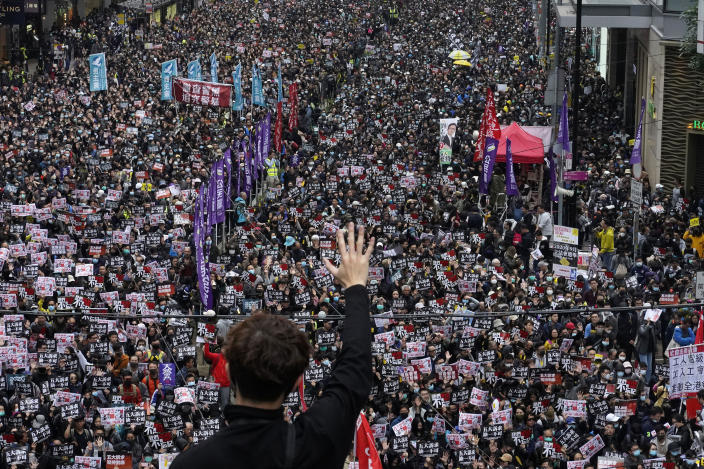 in this Jan. 1, 2020, photo, a protester shows a five demands gesture as Hong Kong people participate in their annual pro-democracy march to insist their five demands be matched by the government in Hong Kong. The city's often-tumultuous street protests had already slowed in the past two months. Now they have ground to an almost complete halt as attention focuses on how to avoid a recurrence of the SARS pandemic, which killed about 300 people in Hong Kong in 2002-03. (AP Photo/Vincent Yu)