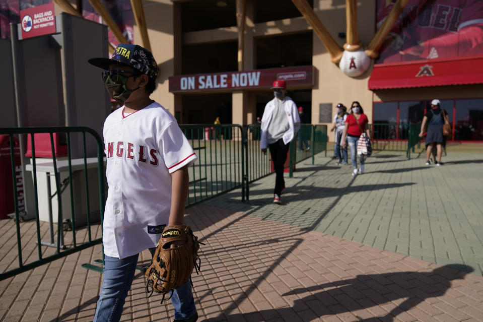 Fans leave Angel Stadium when a baseball game between the Minnesota Twins and the Los Angeles Angels was postponed Saturday, April 17, 2021, in Anaheim, Calif. MLB said the game was postponed to allow for continued COVID-19 testing and contact tracing involving members of the Twins organization. (AP Photo/Ashley Landis)