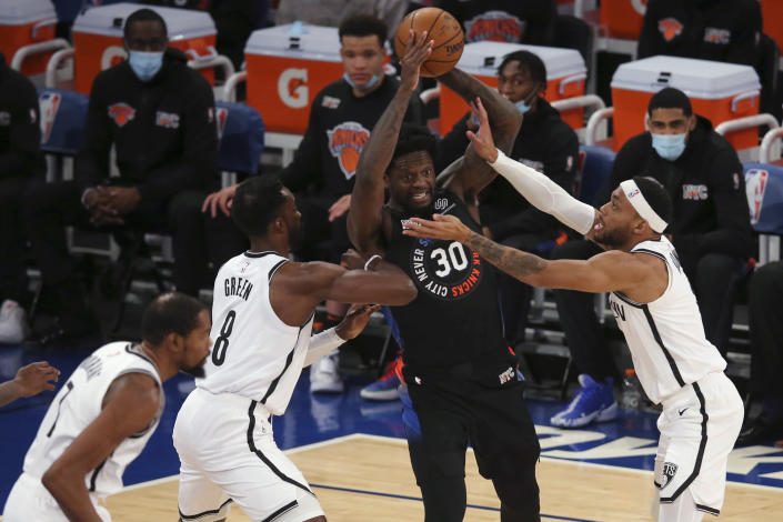 New York Knicks forward Julius Randle (30) looks to pass the ball while defended by Brooklyn Nets forward Jeff Green (8) and guard Bruce Brown, right, during the first quarter of an NBA basketball game Wednesday, Jan. 13, 2021, in New York. (Brad Penner/Pool Photo via AP)
