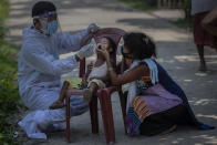 An Indian health worker in protective suit takes the swab of a child to test for COVID-19 in Burha Mayong village, Morigaon district of Assam, India, Saturday, May 22, 2021. (AP Photo/Anupam Nath)