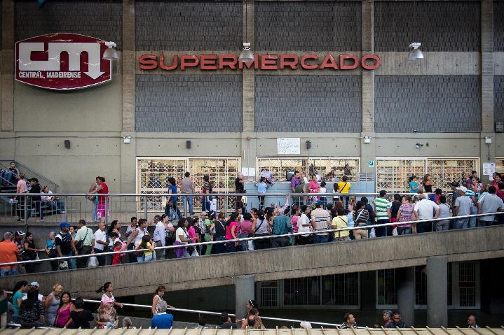 People queue up outside a supermarket in Caracas on January 13, 2015 (AFP Photo/Federico Parra )