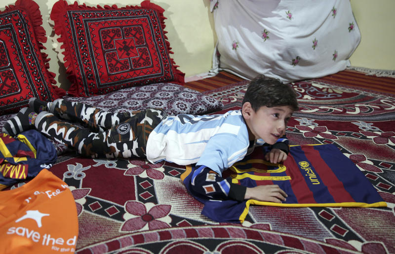 Murtaza Ahmadi, a Lionel Messi fan, poses with Lionel Messi's shirt, at his relative's home in Kabul, Afghanistan, Friday, Dec. 7, 2018. A young Afghan soccer fan who shot to fame after he was photographed in a Messi shirt made from a plastic bag has been forced to flee with his family to the capital after criminal gangs and the Taliban threatened to kill or kidnap him, his mother said Friday. (AP Photo/Massoud Hossaini)