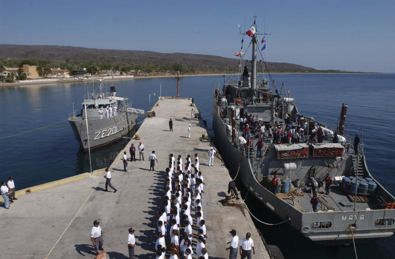 FILE - In this May 12, 2005 file photo, inmates line up on the pier after arriving at the Islas Marias federal prison island, located 90 miles south of Mazatlan, Mexico. President Andres Manuel Lopez Obrador said on Monday, Feb. 18, 2019 that he will close the famed island penal colony and will have it converted into a cultural and environmental education center. (AP Photo/Eduardo Verdugo, File)