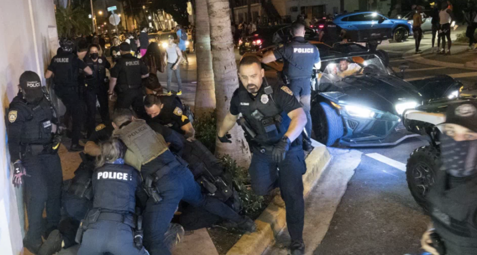 Police officers from the Miami Beach Police Department enforce a curfew during Spring Break.