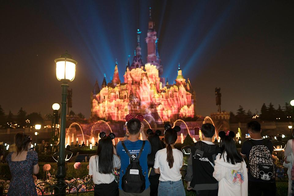 This image shows Disneyland and night while people look at lights behind the castle.