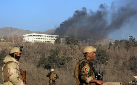 Afghan security personnel stand guard as black smoke rises from the Intercontinental Hotel after an attack in Kabul - Credit: AP Photo/Rahmat Gul