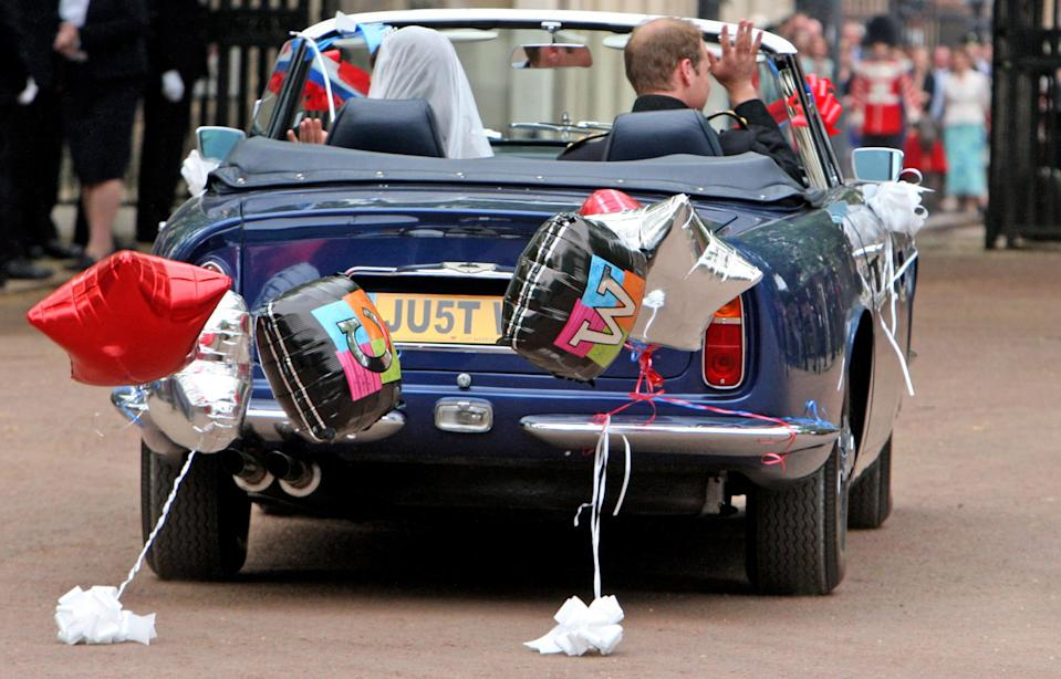 LONDON, ENGLAND - APRIL 29:  Prince William, Duke of Cambridge and Catherine, Duchess of Cambridge drive from Buckingham Palace to Clarence House in a vintage Aston Martin on April 29, 2011 in London, England. The marriage of the second in line to the British throne was led by the Archbishop of Canterbury and was attended by 1900 guests, including foreign Royal family members and heads of state. Thousands of well-wishers from around the world have also flocked to London to witness the spectacle and pageantry of the Royal Wedding.   (Photo by Chris Radburn - WPA Pool/Getty Images)