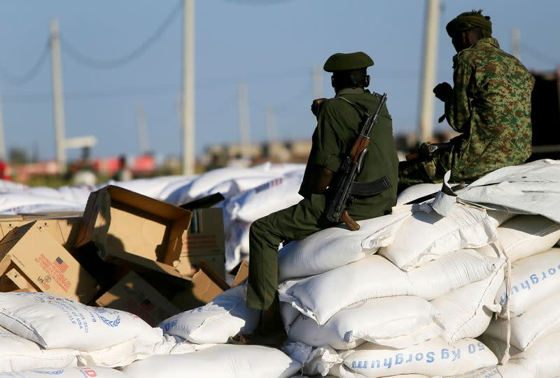 Armed men guard sacks of food delivered to Ethiopian refugees fleeing from the ongoing fighting in Tigray region, at the Fashaga camp, on the Sudan-Ethiopia border, in Kassala state