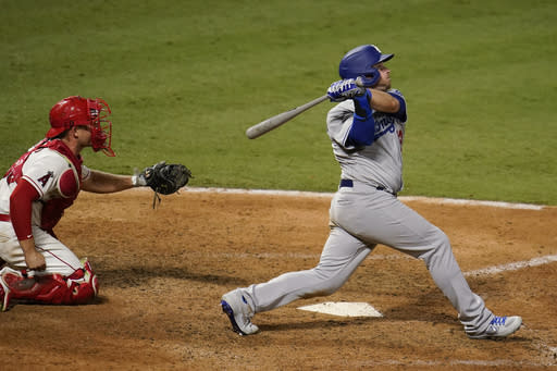 Los Angeles Dodgers' Max Muncy watches his RBI sacrifice fly during the 10th inning of the team's baseball game against the Los Angeles Angels on Saturday, Aug. 15, 2020, in Anaheim, Calif. The Dodgers won 6-5 in 10 innings. (AP Photo/Marcio Jose Sanchez)