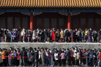 Visitors wearing face masks to help curb the spread of the coronavirus line up to enter an exhibition held at the Forbidden City in Beijing, Saturday, Nov. 7, 2020. China on Saturday reported over a two dozen new confirmed coronavirus infections, all of which the National Health Commission said were in patients who contracted the virus abroad. (AP Photo/Andy Wong)