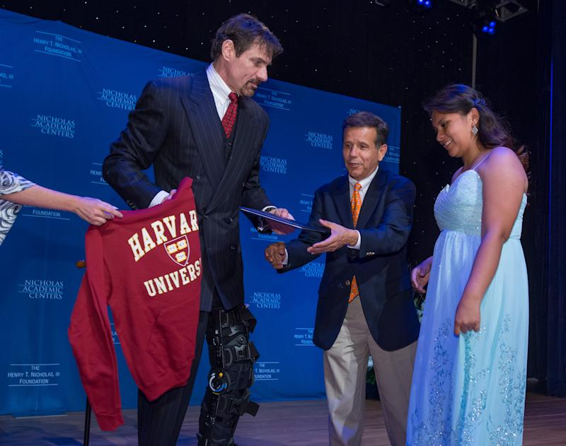 IMAGE DISTRIBUTED FOR NICHOLAS ACADEMIC CENTERS - Nicholas Academic Center Graduate, Aileen Navarrete, a Harvard-bound, Bill Gates Millennium Scholarship recipient, accepts her college sweatshirt and diploma from Dr. Henry T. Nicholas III, left, and Santa Ana Mayor Miguel Pulido during the 2015 Graduation ceremony at the Disneyland Hotel in Anaheim, Calif., Saturday, May 30, 2015. 100 percent of NAC graduates are accepted into a college or university. (Eric Reed/AP Images for Nicholas Academic Centers