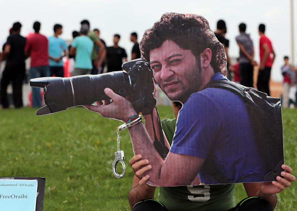 A Bahraini photographer holds up a cutout picture of jailed photographer Ahmed Humaidan in 2014. (Hasan Jamali/AP)